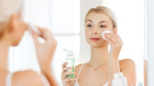 beauty, skin care and people concept - smiling young woman applying lotion to cotton disc for washing her face at bathroom; Shutterstock ID 388715125; PO: today.com